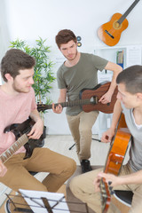 group of friends playing guitar at home