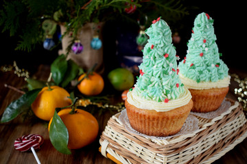 Cupcakes decorated with cream forming Christmas fir trees on a wicker basket surrounded by festive attributes on a wooden table