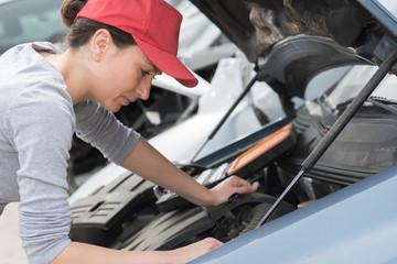 female mechanic fixing a car