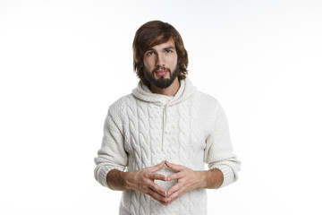 Confident handsome young bearded man wearing casual hooded sweater clasping hands on his stomach and looking at camera with positive expression while trying to persuade someone to do something