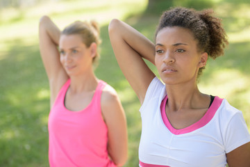 two girlfriends having arms stretching exerciseq