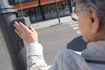 old lady pressing button at traffic lights on pedestrian crossing