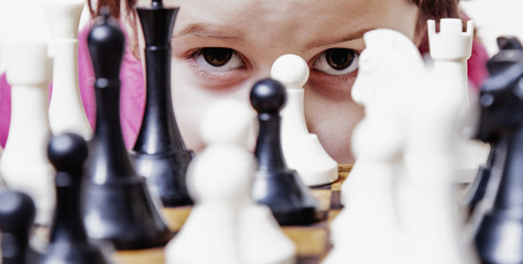 Young beautiful caucasian child girl with chess. (Development, learning, childhood, wunderkind concept)