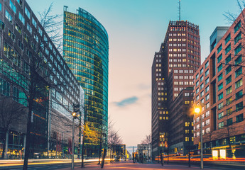 street at potsdamer platz in the night with lens flares from driving cars