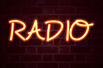 Radio neon sign on brick wall background. Fluorescent Neon tube Sign on brickwork Business concept for Media and Education 3D rendered