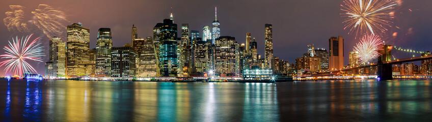 Brightly colorful fireworksNew York City manhattan buildings skyline night evening