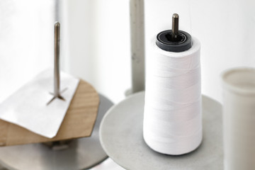 a spool of white thread stands on a dusty stand of sewing machine.