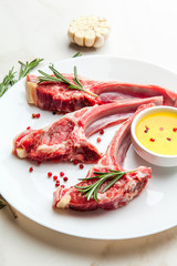 Raw lamb ribs with ingredients for cooking on white marble table