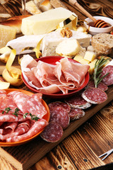 assorted cheese,meats and bread on wooden background