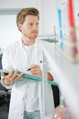 scientist in laboratory taking notes