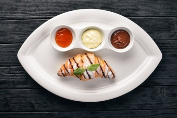 Croissant with sweet sauces. Chocolate, Vanilla and Peach. On a wooden background. Top view.