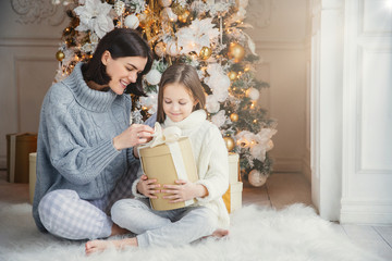 Portrait of pretty girl and beautiful female mother sit together on warm carpet, hold present box, enjoy decorated New Year tree. Family spend time together. Celebration and holidays concept