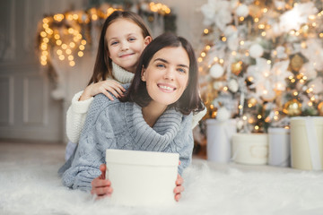 Indoor shot of mother and daughter have fun together, share presents, being in room decorated with garlands and Christmas tree, have joyful expressions, enjoy weekends and winter holidays