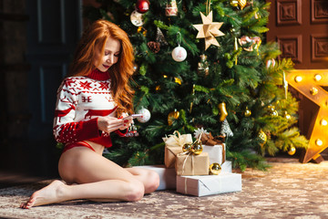 Sexy model lingerie with mobile phone against new year tree