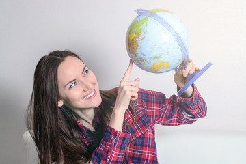 Happy young brunette woman dreams about traveling on vacation with a globe in hands on a white sofa in the room