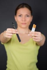 e-cigarette vs tabacco in womans hand