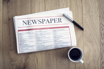 Reading newspaper and drinking coffee on wooden background