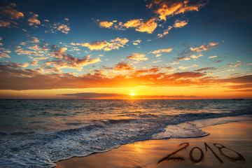 Happy New Year 2018 concept, lettering on the beach. Sea sunrise.
