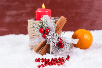 Red candle, tangerines and Christmas decor in the snow