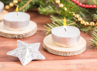 Hot candle against the background of spruce branches