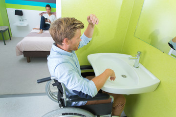 Handicapped man at sink in hotel room