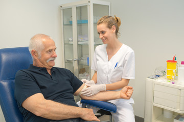 doctor collecting senior patients blood for test in hospital