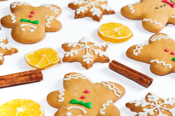 Christmas gingerbread men and snowflakes with lemon and cinnamon sticks on white background. A symbol of winter and new year holidays.