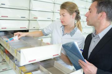 pharmacist looking at medicine package in pharmacy