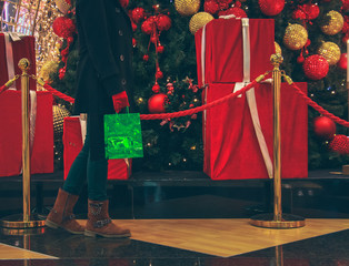 woman holding a gift bag walking on christmas tree in shopping center