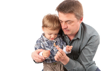 Dad showing a hearing aid to his toddler son. Isolated on white background.
