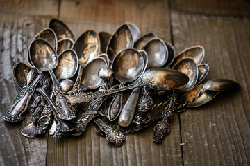 Antique spoons on wooden background.