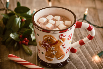 Hot chocolate with marshmallows on wood background with twinkle lights.