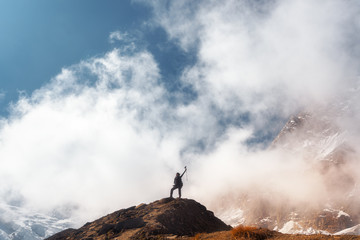 Standing young woman with raised up arms on the mountain peak against blue sky with low clouds in bright day. Landscape with happy girl on the hill, snowy mountains in Nepal. Travel in Himalayas