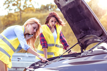 Two beautiful women having trouble with car.