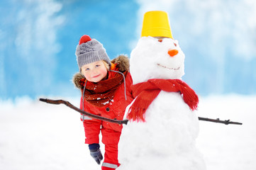 Little boy in red winter clothes having fun with snowman in snowy park