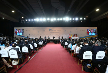 A video of Chile's President Michelle Bachelet is seen on TV screens during the opening ceremony of the World Trade Organization's ministerial conference in Buenos Aires
