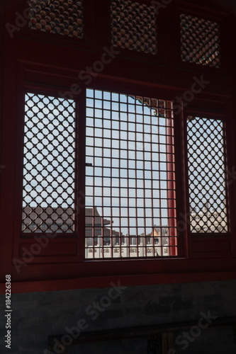 lattice window looking over the forbidden city beijing china stock