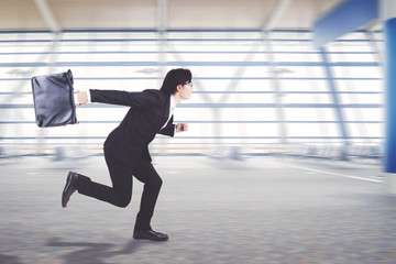 Young businessman running on the airport terminal