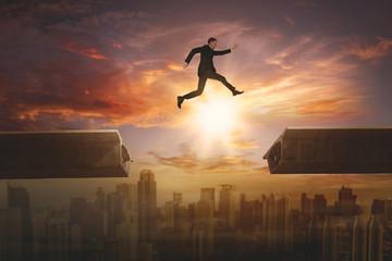 Male entrepreneur jumping gap on the bridge