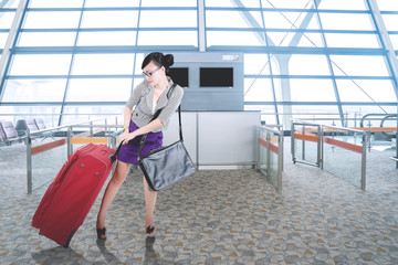 Beautiful businesswoman pulling a suitcase at airport