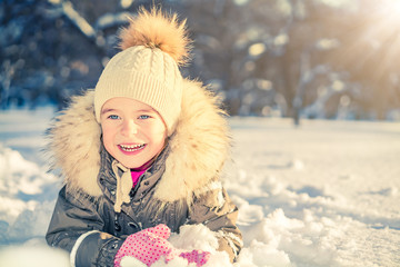 Little girl playing with snow in sunny winter park