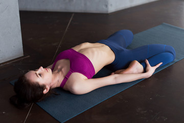 Pretty Caucasian girl wearing sports bra and leggings doing stretching yoga exercise lying in reclining hero pose on mat in studio