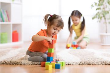 Kids playing block toys in playroom at nursery