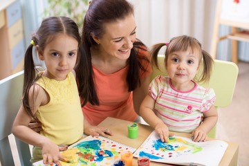 Mother and daughters are painting together. Happy family are coloring with paintbrush. Woman and children have a fun pastime.