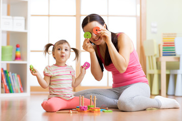 Mother and daughter play on floor having a fun pastime