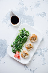 Plate with fried asian seafood dumplings served with chuka salad, white cement background, above view