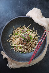Pork meat with udon noodles in a wok pan over scratched metal background, above view, vertical shot