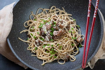 Pork meat cooked in honey sauce with green onion, sesame and udon noodles in a wok, studio shot