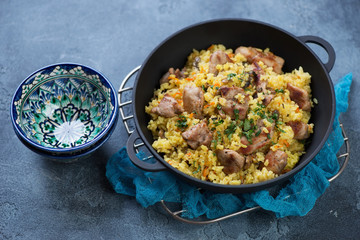 Cast-iron pan with pilaf and pialas over blue stone background, studio shot