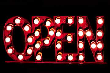 Rusty grunge luminous red color sign Open decorated  light bulbs isolated on black background